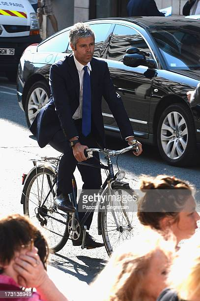 Laurent Wauquiez rides a bicycle as he leaves the UMP headquarters after an extraordinary meeting of UMP rightwing opposition party July 8 2013 in...