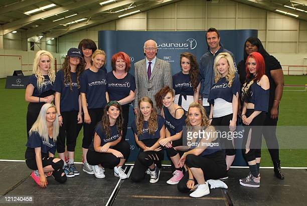Laureus Academy Member Sir Bobby Charlton and Laureus Ambassador Michael Vaughan stand for a picture with a group of street dancers during their...