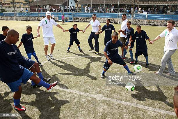 Laureus Ambassador Axel Schulz plays football with the local children at the MercedesBenz Sprinter handover to the Bola Project during 2013 Laureus...