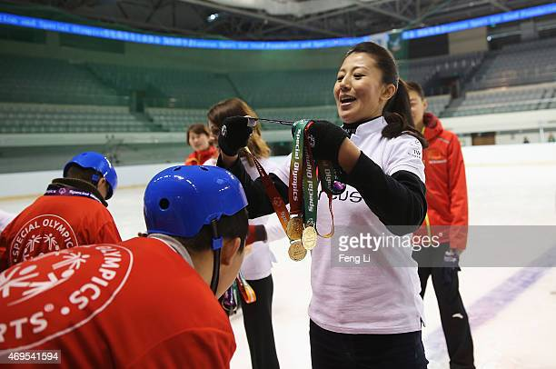Laureus World Sports Academy member Yang Yang gives a child a medal during a visit to a Laureus Sport For Good Project prior to the Laureus World...