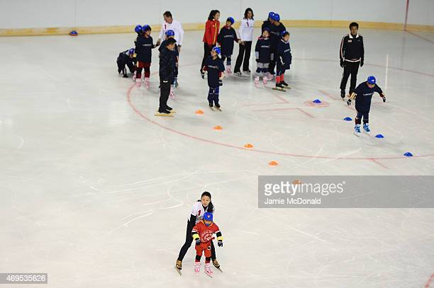 Laureus World Sports Academy member Yang Yang helps a young child as she visits a Laureus Sport For Good Project prior to the Laureus World Sports...