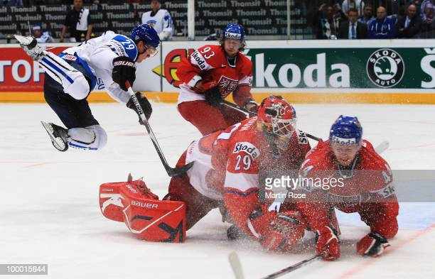 Lauri Korpikoski of Finland jumps over goaltender Tomas Vokoun of Czech Republic during the IIHF World Championship quarter final match between...