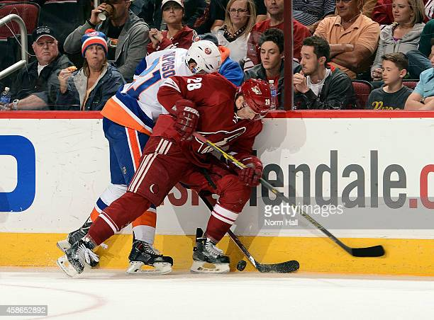 Lauri Korpikoski of the Arizona Coyotes and Kyle Okposo of the New York Islanders battle for the puck along the boards during the second period at...
