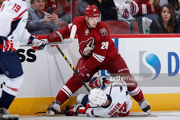 Lauri Korpikoski of the Arizona Coyotes stands over Mike Green of the Washington Capitals after a body check during the second period of the NHL game...