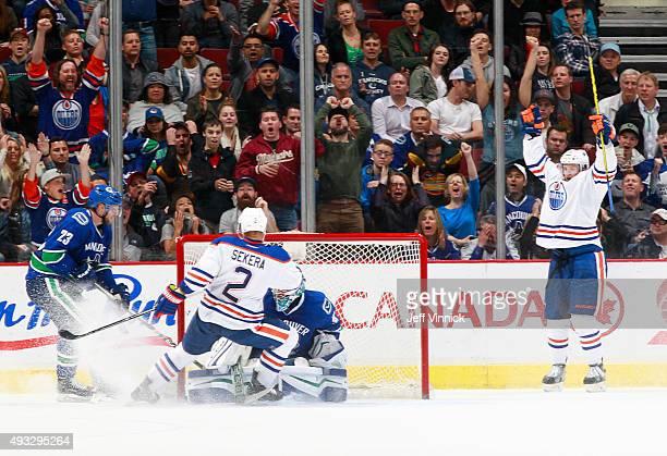 Lauri Korpikoski of the Edmonton Oilers celebrates his overtime goal against Ryan Miller of the Vancouver Canucks with Alexander Edler of the Canucks...