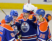 Lauri Korpikoski of the Edmonton Oilers is mobbed by teammates after scoring a hat trick against the New York Rangers at Rexall Place on December 11...