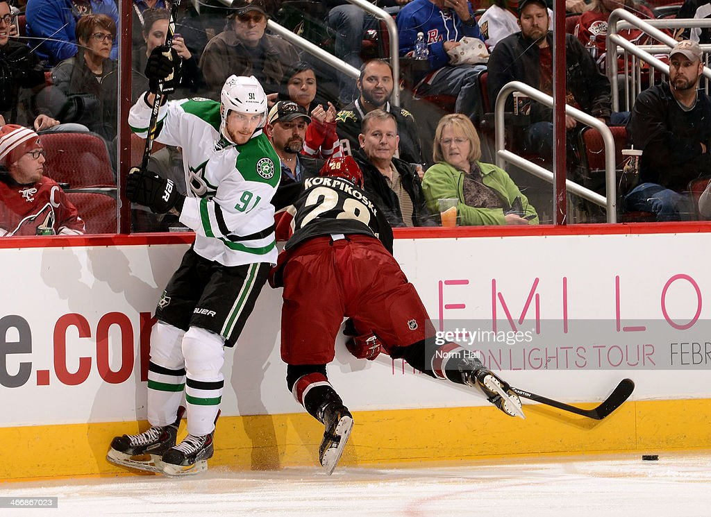 Lauri Korpikoski #28 of the Phoenix Coyotes falls into the boards as he attempts to check Tyler Seguin #91 of the Dallas Stars during the first period at Jobing.com Arena on February 4, 2014 in Glendale, Arizona.
