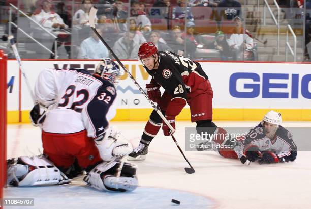 Lauri Korpikoski of the Phoenix Coyotes shoots the puck wide of goaltender Mathieu Garon and Kris Russell of the Columbus Blue Jackets during the...