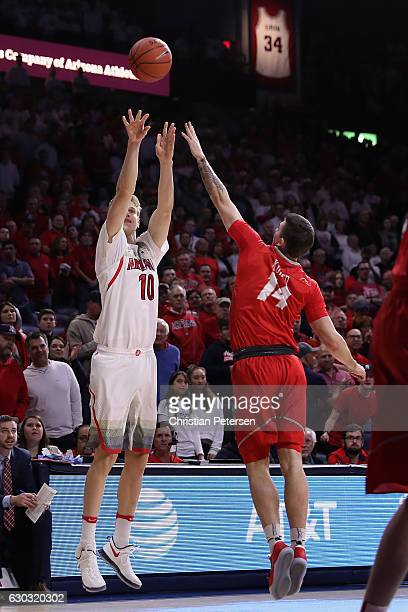 Lauri Markkanen of the Arizona Wildcats attempts a three point shot over Dane Kuiper of the New Mexico Lobos during the first half of the college...