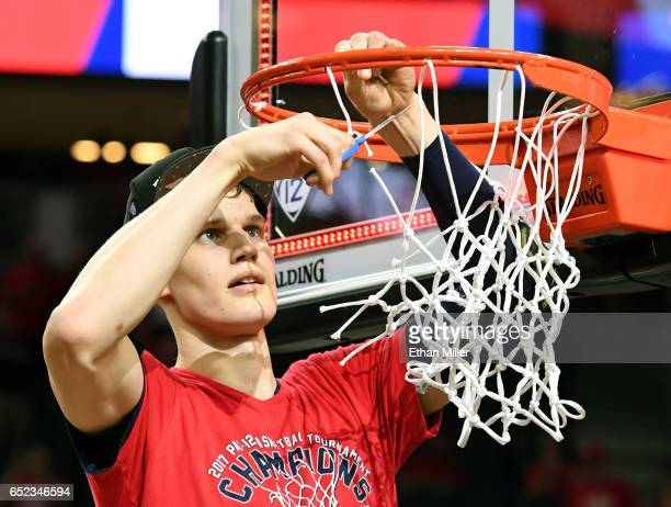 Lauri Markkanen of the Arizona Wildcats cuts down a piece of a net after defeating the Oregon Ducks 8380 to win the championship game of the Pac12...