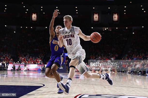 Lauri Markkanen of the Arizona Wildcats drives the ball past Matt Smith of the Cal State Bakersfield Roadrunners during the first half of the college...
