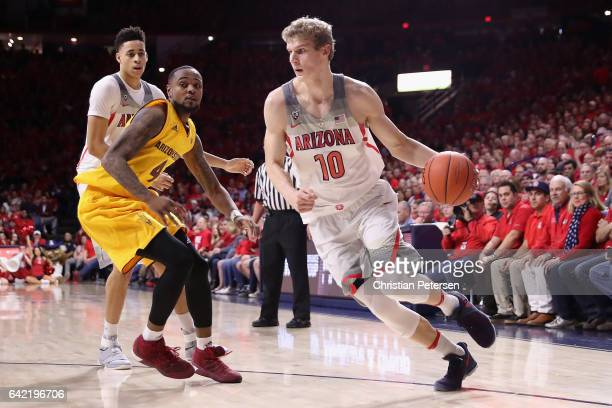 Lauri Markkanen of the Arizona Wildcats drives the ball past Torian Graham of the Arizona State Sun Devils during the first half of the college...