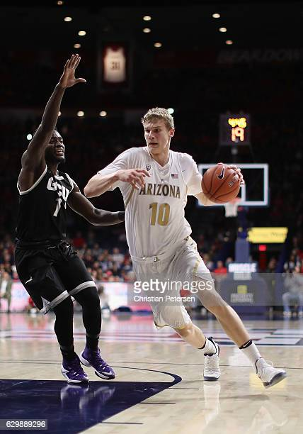 Lauri Markkanen of the Arizona Wildcats moves the ball past Fiifi Aidoo of the Grand Canyon Lopes during the first half of the college basketball...