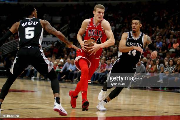 Lauri Markkanen of the Chicago Bulls dribbles the ball between Dejounte Murray and Danny Green of the San Antonio Spurs in the first quarter at the...