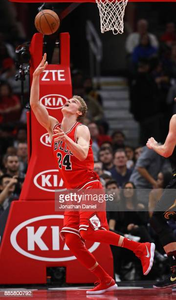 Lauri Markkanen of the Chicago Bulls gets off a shot against the Cleveland Cavaliers at the United Center on December 4 2017 in Chicago Illinois NOTE...