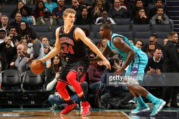 Lauri Markkanen of the Chicago Bulls handles the ball against Marvin Williams of the Charlotte Hornets on December 8 2017 at Spectrum Center in...