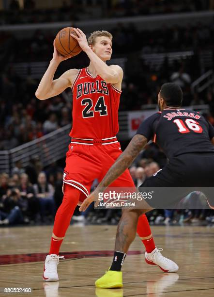 Lauri Markkanen of the Chicago Bulls looks to pass over James Johnson of the Miami Heat at the United Center on November 26 2017 in Chicago Illinois...