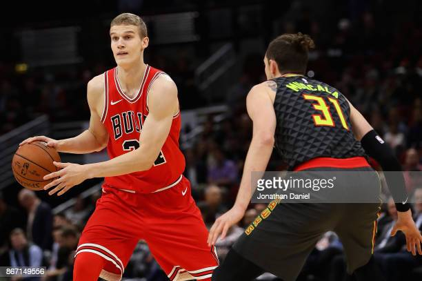 Lauri Markkanen of the Chicago Bulls moves against Mike Muscala of the Atlanta Hawks at the United Center on October 26 2017 in Chicago Illinois The...