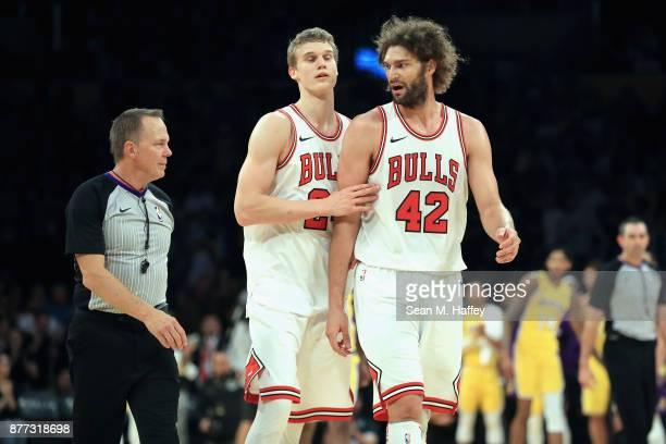Lauri Markkanen pushes Robin Lopez of the Chicago Bulls away from referee Bill Spooner during the second half of a game against the Los Angeles...