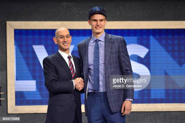 Lauri Markkanen smiles with Adam Silver after being selected seventh overall by the Minnesota Timberwolves at the 2017 NBA Draft on June 22 2017 at...