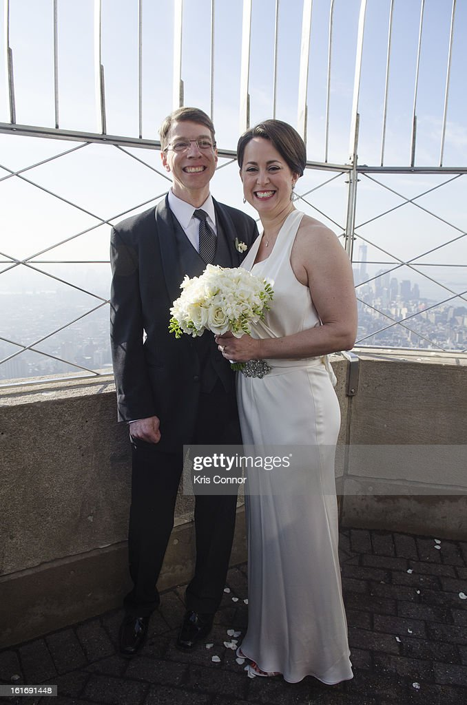 Laurie Ann Phillips and Daniel Rosenthal of Washington DC take photos and speak with the press after being married as part of the Empire State Building Hosts Valentine's Day Weddings ceremony at The Empire State Building on February 14, 2013 in New York City.