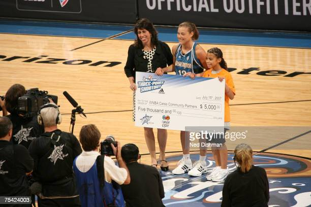 Laurie Koehn of the Washington Mystics is awarded a check by WNBA President Donna Orender following her victory in the 3 Point Shootout prior to the...