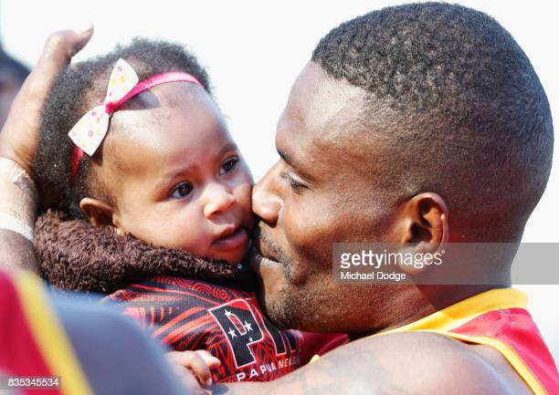 Laurie Logo of Papua New Guinea celebrates the win with his daughter during the 2017 AFL International Cup Grand FInal match between New Zealand and...