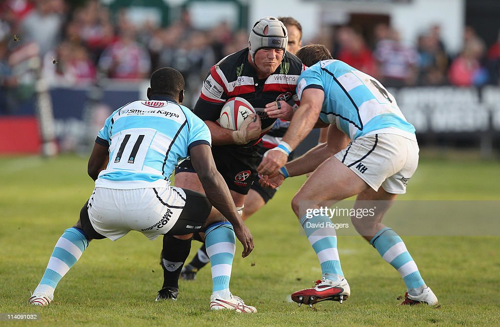 Laurie McGlone of Cornish Pirates is tackled by Miles Benjamin and Kai Horstmann during the RFU Championship playoff final 1st Leg match between...