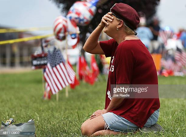 Laurie Norman is overcome with emotion as she pays her respects to those killed while visiting a memorial placed in front of the Armed Forces Career...