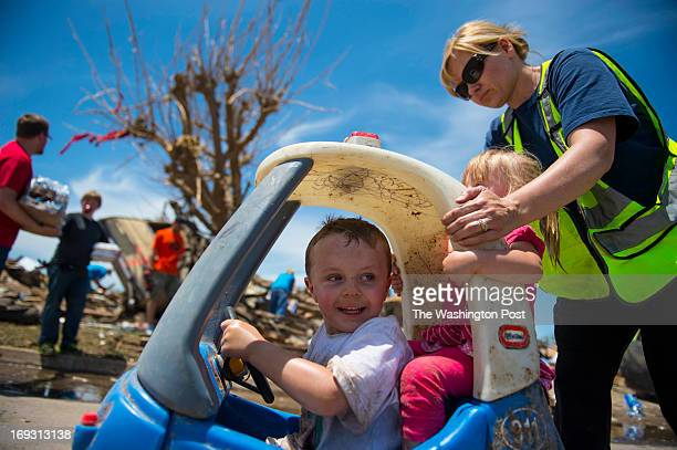 Laurie Stang of the Sperry Fire Department push around Mason Taylor and his sister Mallory Taylor in a kiddie car as family members pick through...