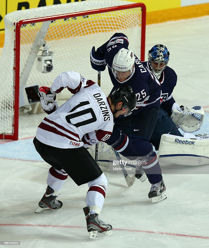 Lauris Darzins (L) of Latvia and Matt Carle (R) of USA battle for the puck during the IIHF World Championship group H match between Latvia and USA at Hartwall Areena on May 5, 2013 in Helsinki, Finland.