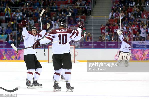 Lauris Darzins of Latvia celebrates with his teammates after scoring an open net goal late in the third period against Switzerland during the Men's...
