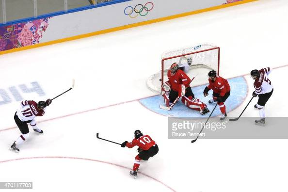 Lauris Darzins of Latvia scores a goal in the first period against Jonas Hiller of Switzerland during the Men's Ice Hockey Qualification Playoff game...