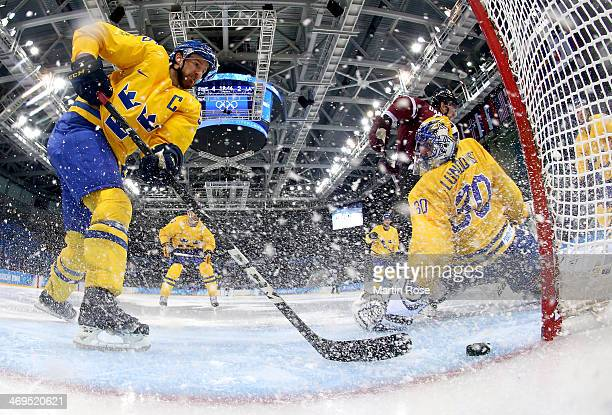 Lauris Darzins of Latvia shoots against Niklas Kronwall and Henrik Lundqvist of Sweden in the second period during the Men's Ice Hockey Preliminary...