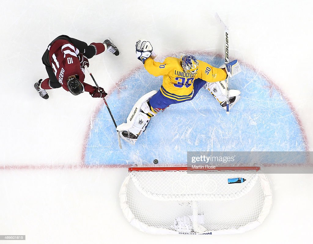 Lauris Darzins #10 of Latvia shoots and scores against Henrik Lundqvist #30 of Sweden in the first period during the Men's Ice Hockey Preliminary Round Group C game on day eight of the Sochi 2014 Winter Olympics at Shayba Arena on February 15, 2014 in Sochi, Russia.
