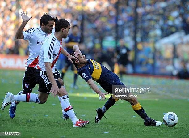 Lautaro Acosta of Boca Juniors struggles for the ball with Leandro González Pirez and Gabriel Mercado of River Plate during a match between Boca...