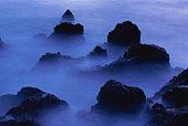 Lava rocks and ocean shrouded in fog, dawn (long exposure)