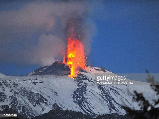 Lava spews from a crater of the giant Etna Volcano on the southern Italian island of Sicily on January 6 2012 A column of hot ash spewed high into...