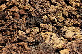 Natural solidified formations volcanic lava background. Cracks pattern texture brown magma stone. Pumice very light porous volcanic rock