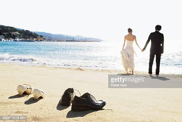 Lavandu, France, groom and bride walking on beach, rear view