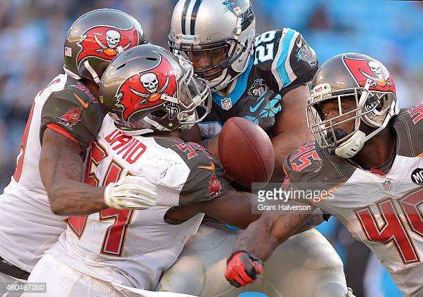 Lavonte David and Orie Lemon of the Tampa Bay Buccaneers knock the ball loose from Jonathan Stewart of the Carolina Panthers during their game at...