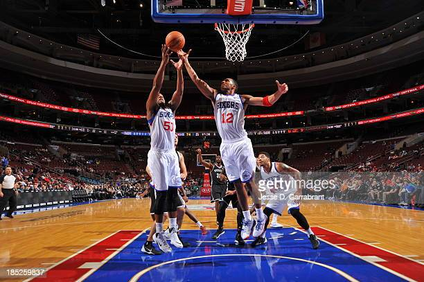 Lavoy Allen and Evan Turner of the Philadelphia 76ers goes up for a rebound against the Brooklyn Nets at the Wells Fargo Center on October 14 2013 in...