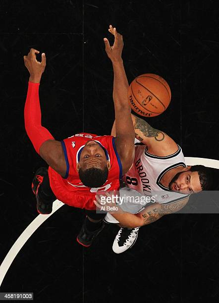 Lavoy Allen of the Philadelphia 76ers and Deron Williams of the Brooklyn Nets in action during their game at the Barclays Center on December 16 2013...