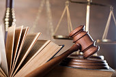 Jugde mallet and scale of justice on wooden table