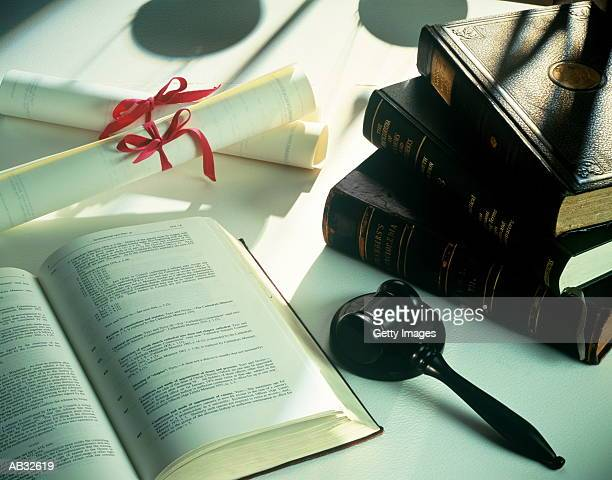 Law books, gavel and scrolls on table, close-up
