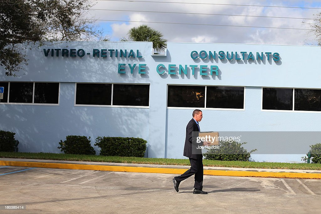 A law enforcement agent walk by a building as he along with FBI agents and other law enforcement officials investigate at the medical-office complex of Dr. Salomon Melgen who has possible ties to U.S. Sen. Bob Menendez (D-NJ) on January 30, 2013 in West Palm Beach, Florida. The agents arrived last night at the medical-office complex and started hauling away potential evidence in several vans.