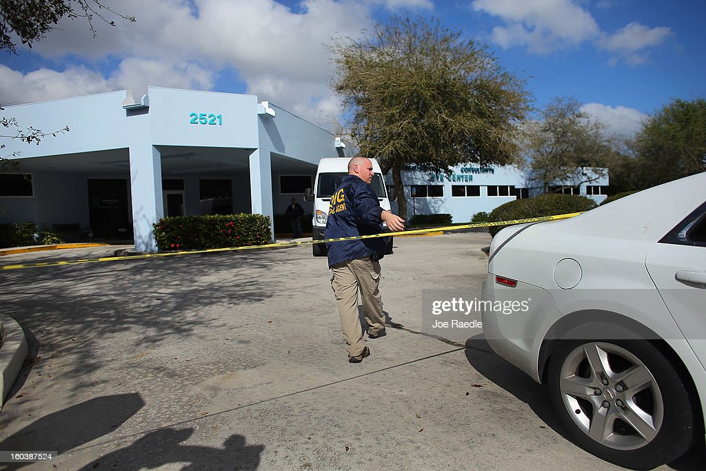 A law enforcement agent walks outside a building as the FBI and others investigate at the medical-office complex of Dr. Salomon Melgen who has possible ties to U.S. Sen. Bob Menendez (D-NJ) on January 30, 2013 in West Palm Beach, Florida. The agents arrived last night at the medical-office complex and started hauling away potential evidence in several vans.