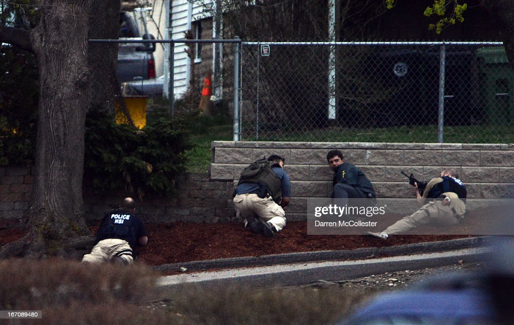 Law enforcement approach an area where a suspect is hiding on Franklin St on April 19 2013 in Watertown Massachusetts After a car chase and shoot out...
