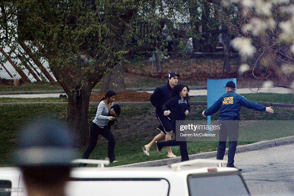 Law enforcement evacuate people away from an area reportedly where a suspect is hiding on April 19 2013 in Watertown Massachusetts After a car chase...