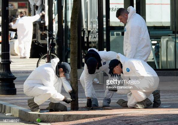 Law enforcement investigators work near the finsh line of the Boston Marathon on Boylston Street looking for evidence after last Monday's bombings...